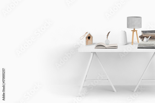 Fototapeta pure and white decorated table with stack of books