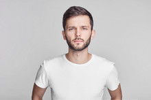 Close Up Portrait Of Good-looking Serious Bearded Caucasian Man With Blue Beautiful Eyes Wearing White Casual T-shirt Posing Isolated On Gray Studio Wall With Copy Space For Your Promotional Content.