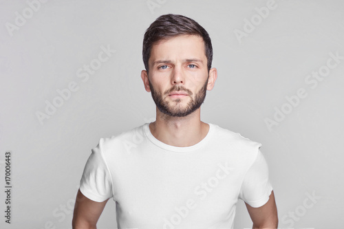 Close up portrait of good-looking serious bearded Caucasian man with blue beautiful eyes wearing white casual t-shirt posing isolated on gray studio wall with copy space for your promotional content Fototapet