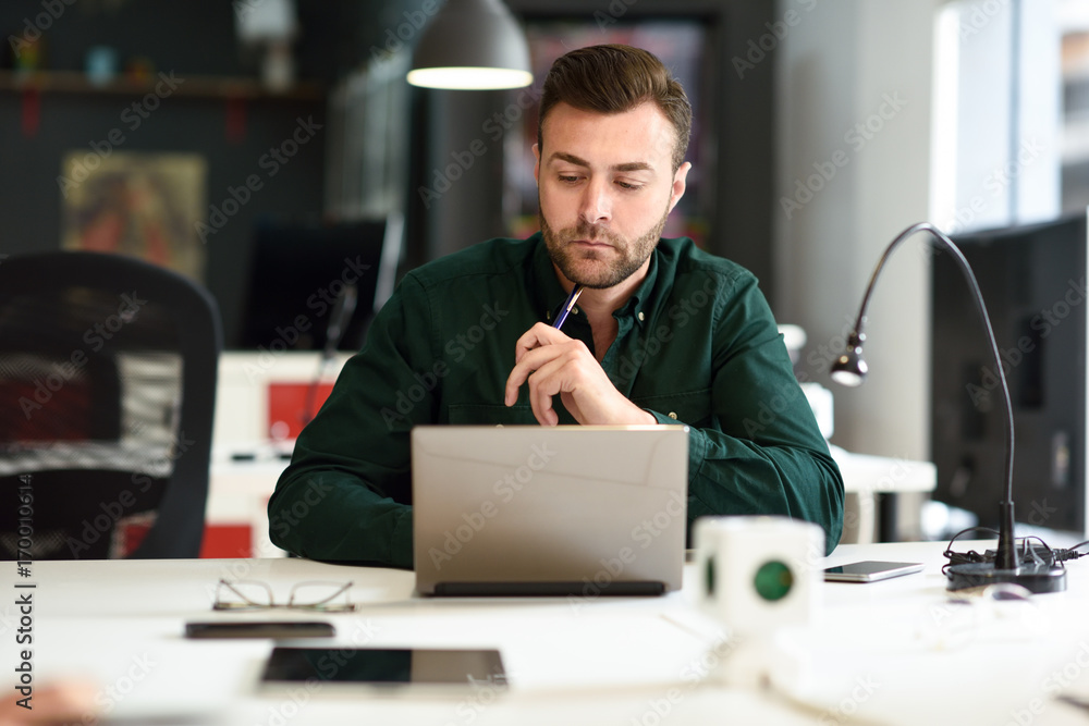 Fototapeta Young man studying with laptop computer on white desk.