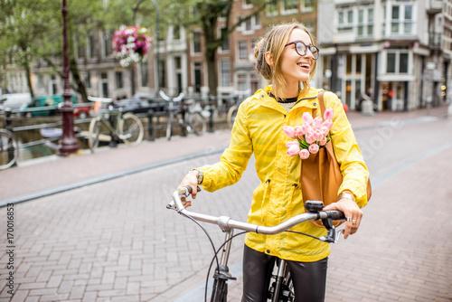 Fototapeta premium Młoda kobieta w żółtym płaszczu przeciwdeszczowym z torbą i kwiatami, jazda na rowerze w mieście Amsterdam
