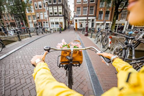 Fototapeta premium Kobieta na rowerze z bukietem kwiatów na ulicy w mieście Amsterdam. Zobacz na rękach trzymających hełm