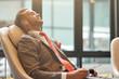 Leinwanddruck Bild - Professional businessman having a nap in the departure lounge