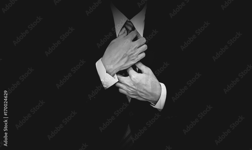 Fototapeta Businessman in black suit on black background, black and white