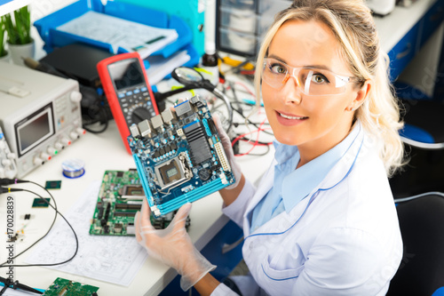 Fotografiet  Female electronic engineer holding computer motherboard in hands in the laborato