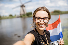 Portrait Of A Young Woman Tourist Standing With Dutch Flag On The Beautiful Landscape Background With Old Windmills In Netherlands