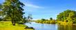 Leinwandbild Motiv Sommerliche Landschaft mit Wiesen und Fluss