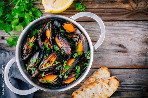 Staande foto Schaaldieren Delicious seafood mussels with with sauce and parsley. Lemon and baguette . Clams in the shells.