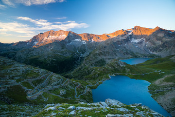 High altitude alpine lake, dams and water basins in idyllic land with majestic rocky mountain peaks glowing at sunset. Road leading to mountain pass on the Alps.