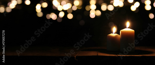 Fototapeta  Burning candles over black background with bokeh glitter lights