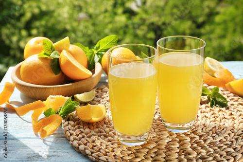 Fotografie, Obraz  Glasses with delicious orange juice and ingredients on table outdoors