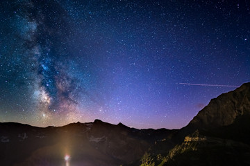 The colorful glowing Milky Way arch and the starry sky from high up on the Alps.