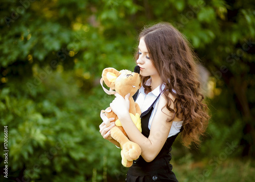 Fototapeta An innocent young brown-haired woman in a forest with a plush toy. obraz na płótnie