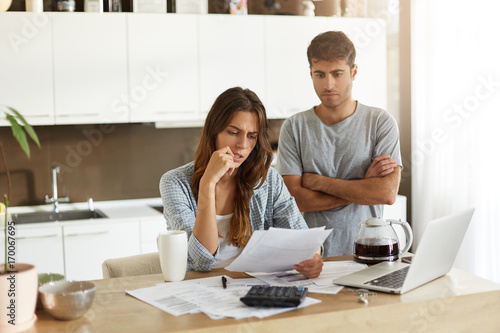 Fototapeta Candid shot of young American man and woman dressed casually feeling stressed while managing finances in kitchen together, calculating expenses, paying utility bills online on laptop computer obraz