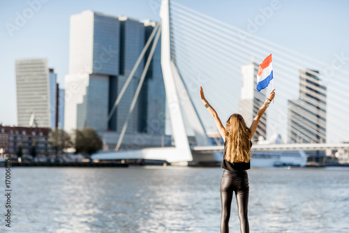 Foto op Canvas Rotterdam Woman with dutch flag enjoying beautiful cityscape view on the modern riverside during the morning in Rotterdam city