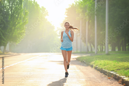 Foto  Morning of young sporty woman running outdoors