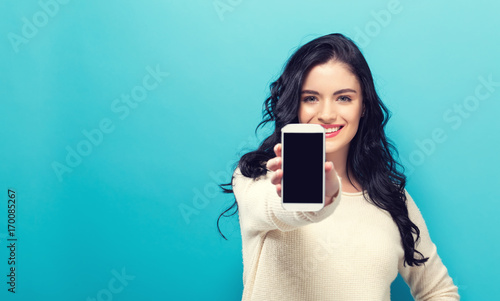 Young woman holding out a cellphone in her hand Fototapet