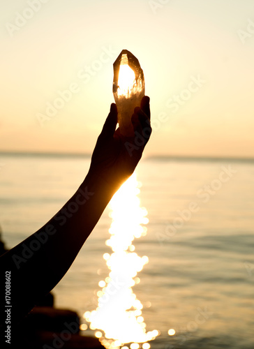 Photo  Young woman's hands holding clear quartz point in front of the lake sunrise