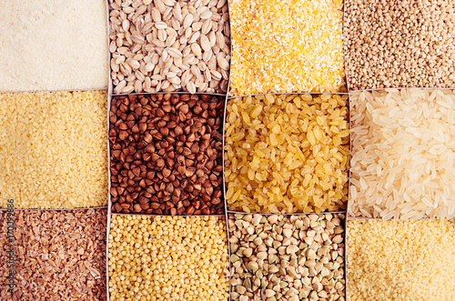 Assortment groats as decorative background. Wheat pearl, bulgur, millet, rice, couscous, semolina, corn grits, buckwheat, quinoa. Top view, closeup.