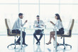 The three business people sit on the conference table