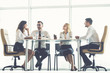 The four business people sit at the office table near the panoramic window