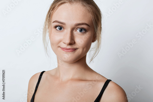 Close up portrait of attractive female with freckled skin, blue eyes and dimples on cheeks, having confident look into camera, isolated over white background Fototapet