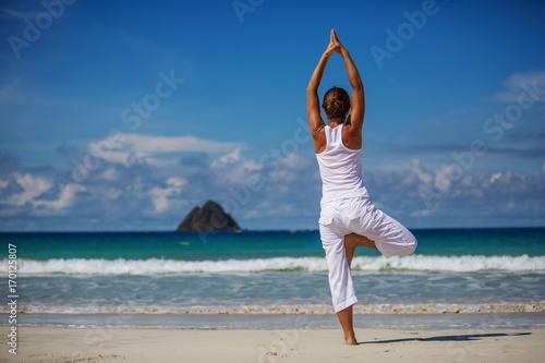 Fotografija  Caucasian woman practicing yoga at seashore of tropic ocean