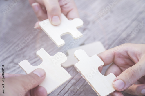Photo  Business partnership or teamwork concept with a business people presenting a matching puzzle piece as they cooperate on finding an answer and solution, close up of their hands