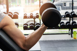 Athlete man training in the gym. A man lifting dumbbell - dumbbell biceps curl