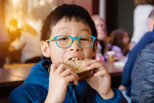 Young Asian Boy Eating Sandwic...