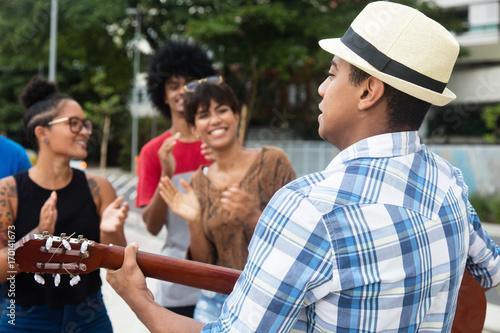 Plakat Radośni słuchający młodzi ludzie przy koncertem uliczny muscian