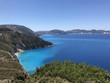 The coast of Kefalonia in Greece with its turquoise sea, blue sky and green mountains.