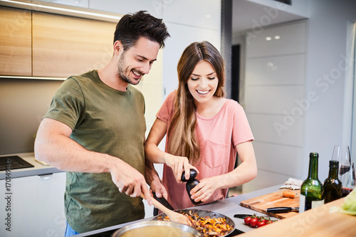 Fototapeta Cute joyful couple cooking together and adding spice to meal, laughing and spending time together in the kitchen obraz