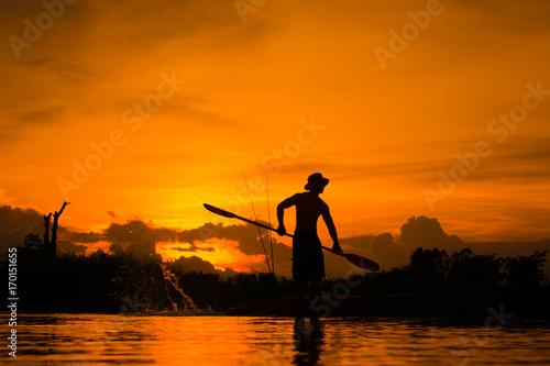 Plakat Sylwetka rybak pozycja na łodzi, chwyta paddle i paddle z pluśnięciem woda na zmierzchu tle.