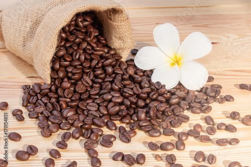 kawowe-fasole-na-drewnianym-stole-z-malym-bialym-kwiatkiem