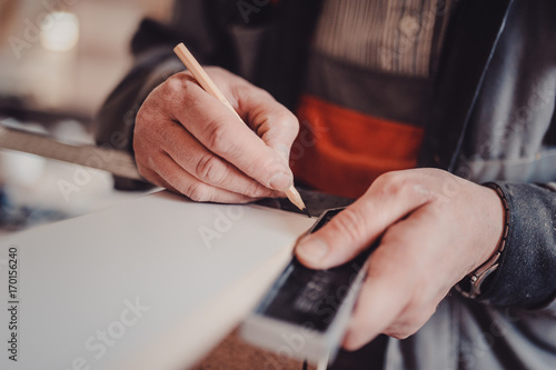 Fototapety, obrazy: A carpenter uses a square for marking a hole in a furniture part