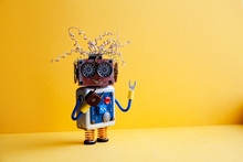 Creative Design Crazy Robot Toy, Electric Wires Hairstyle, Big Eye Glasses, Electronic Circuit Blue Silver Body, Red Heart. Yellow Background. Copy Space