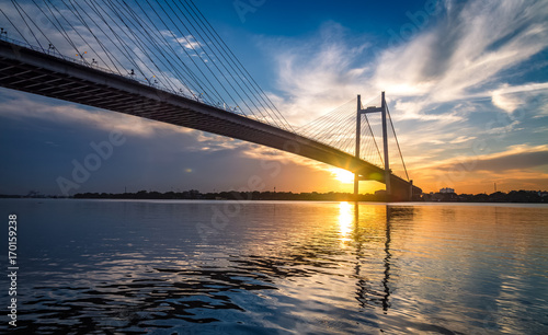 Spoed Foto op Canvas Brug Vidyasagar Setu - the cable stayed bridge on river Hooghly at sunset with moody sky.
