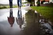 Leinwandbild Motiv Regentage, Menschen spiegeln sich in Pfütze