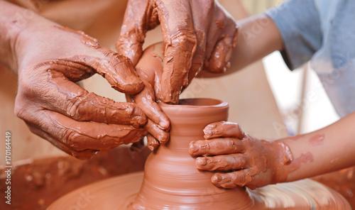 Fotografía manos barro alfarero enseñando a un niño U84A1128-f17