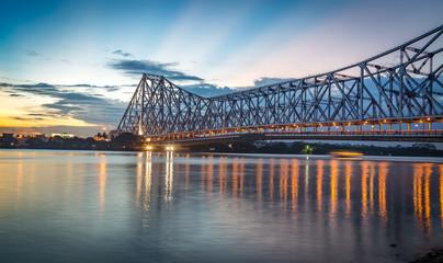 Historic Howrah bridge Kolkata at sunset with moody sky.