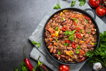 Chili Con Carne In Iron Pan On Black Background. Traditional Mexican Food.