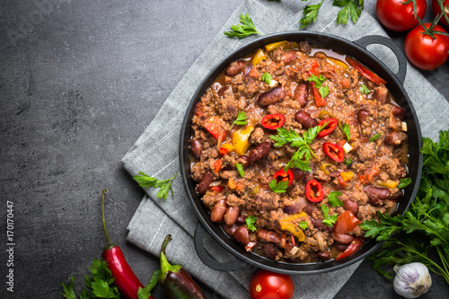 Fotografie, Tablou Chili con carne in iron pan on black background