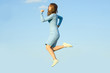 Beautiful young girl in dress jogging in sky jump