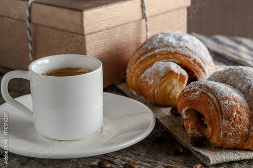 Photo Stands Coffee beans Fresh croissants and coffee on wooden table.
