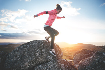 Athletic girl running in the mountains at sunset against the backdrop of a beautiful landscape. Sport tight clothes. Intentional motion blur.
