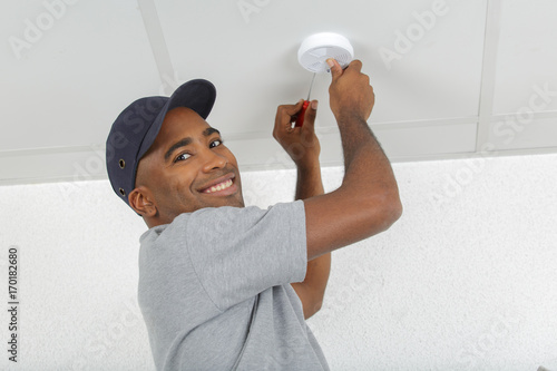 Photo  electrician removing battery from smoke detector