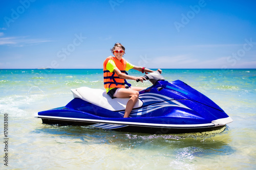 Wall Murals Water Motor sports Teenager on water scooter. Teen age boy water skiing.