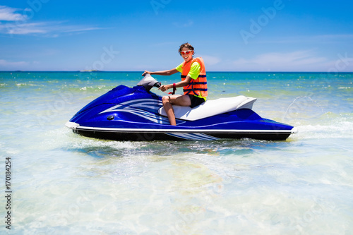 Poster Nautique motorise Teenager on water scooter. Teen age boy water skiing.