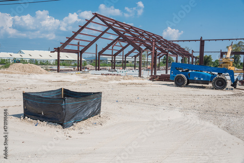 Staande foto Industrial geb. Steel structure of new industrial building under cloud blue sky. New technology structural frame beam of factory in construction. Steel frame manufacturer and crane, telescopic forklift, sand, gravel